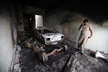 A man stands inside the compound of a house, burned by a mob during clashes between two groups a day earlier in Faisalabad