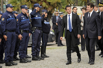 French Interior Minister Valls walk past local policemen following the funeral of slain gendarme officer Briere in Nice