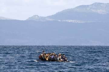 Afghan migrants in an overcrowded raft approach a beach on the Greek island of Lesbos
