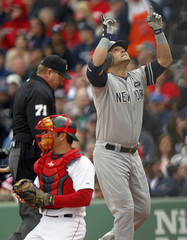 New York Yankees right fielder Nick Swisher points skyward after hitting a solo home run off starting pitcher John Lackey with catcher Jason Varitek in the background during the second inning of their MLB American League baseball game at Fen
