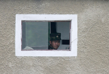 A North Korean soldier looks out from the window of a guard tower along the banks of the Yalu River