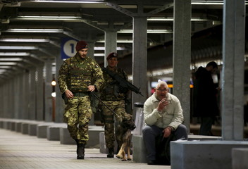 Italian Army soldiers patrol with their dog at the Tiburtina train station in Rome