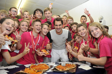Switzerland's Federer poses together with the tournament's ball boys and girls as they eat pizza at the Swiss Indoors ATP tennis tournament in Basel