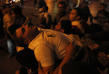 An injured Egyptian protester is carried during clashes in front of the state security headquarters in downtown