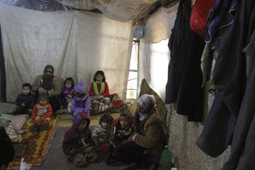 A Syrian refugee woman carries her child as they sit inside a tent near Tripoli
