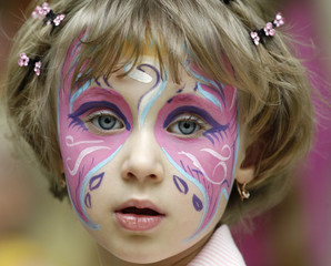 A girl with her face painted takes part during a beauty contest for children during the annual Christmas fair in Russia's Siberian city of Krasnoyarsk