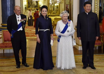 China's President Xi Jinping and his wife Peng Liyuan accompany Britain's Queen Elizabeth and her husband Prince Philip, the Duke of Edinburgh, as they arrive for a state banquet at Buckingham Palace in London, Britain