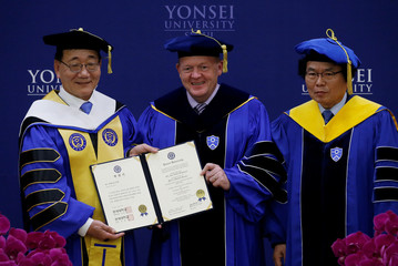 Denmark's PM Lars Lokke Rasmussen poses for photographs after receiving an honorary degree of Doctor of Political Science during a conferment ceremony at Yonsei University in Seoul