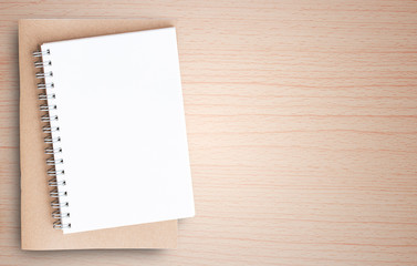 Blank paper notebook on brown wooden table background.