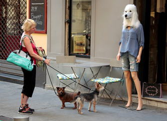 A woman and her dogs stop and look at a store mannequin wearing a dog's head mask outside a fashion shop in Nice
