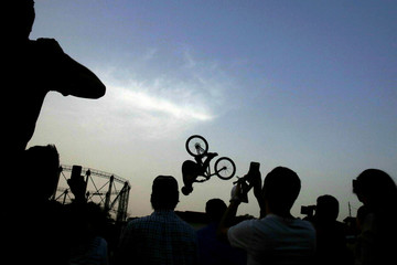 People are silhouetted as they take pictures of a biker performing a backflip jump during the 5th Athens Bike Festival