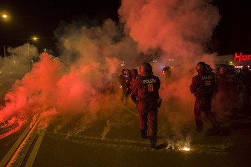 Policemen walk between flares thrown by right wing protesters who are against bringing asylum seekers to an accomodation facility in Heidenau