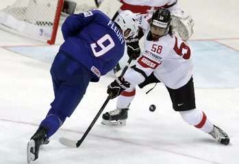 France's Fleury fights for the puck with Switzerland's Blum during their Ice Hockey World Championship game at the O2 arena in Prague