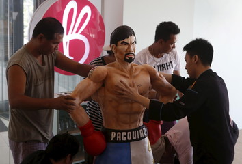 Workers from a bakery display a life-size 70-kg chocolate cake of local boxing icon Manny Pacquiao at a restaurant in Manila
