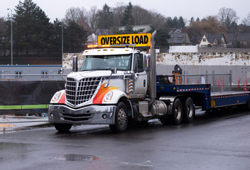 Elegant powerful big rig semi truck with step down flat bed trailer on construction side