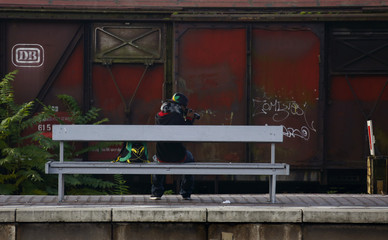 A man takes pictures of birds as he sits in front of an old freight car, belonging to German railway operator Deutsche Bahn, as he waits for a commuter train at the train station in Hanau
