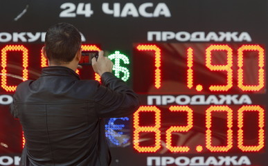 Man takes picture of board showing currency exchange rates of U.S. dollar and euro against Russian rouble in Moscow