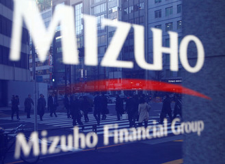 Pedestrians are reflected on Mizuho Bank's signboard in Tokyo