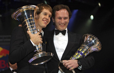Formula One World Champion Vettel of Germany and Red Bull team manager Horner of Britain hold their trophies during the 2010 FIA Prize Giving gala in Monaco