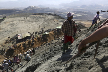Miners search for jade stones at a mine dump at a Hpakant jade mine in Kachin state