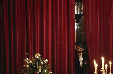 A man looks from behind a curtain during a banquet held in honour of South Korea's President Park Geun-hye at the Guildhall in London