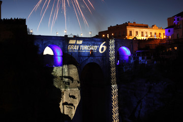 "Fireworks explode over ""Puente Nuevo"" while a portrait of Kazunori Yamauchi is projected during the international presentation of the new ""Gran Turismo 6"" video game in downtown Ronda"