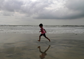 A girl runs through the beach against the backdrop of monsoon clouds at Fort Kochi beach in Kerala
