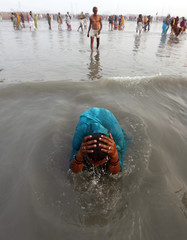 A Hindu pilgrim takes a holy dip at the confluence of the Ganges river and the Bay of Bengal at Sagar Island