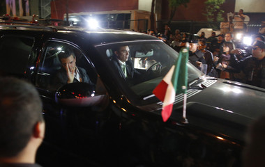 Mexico's President Enrique Pena Nieto (L inside car) waves to the crowd while arriving at the headquarters of state oil giant Pemex in Mexico City