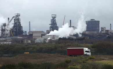A lorry drives past the Tata steelworks in Port Talbot, Wales