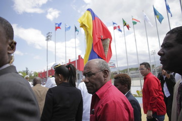 Venezuelan Vice President Aristobulo Isturiz, followed by Haiti's interim Prime Minister Enex Jean-Charles, passes in front of a Hugo Chavez statue covered in a Venezuelan flag at the opening of the Hugo Chavez park in Port-au-Prince, Haiti