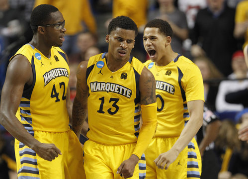 Marquette University's Blue reacts with Otule and Wilson after making shot and drawing foul against Butler University during NCAA basketball game in Lexington