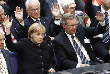 CDU candidate Wulff and German Chancellor Merkel  raise hands during German presidential election at the Reichstag in Berlin