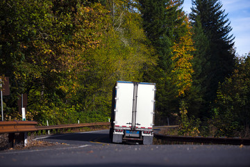 Semi truck trailer back view on winding autumn forest road