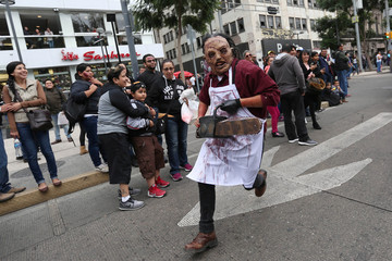 A man dressed as zombie runs as he participates in a Zombie Walk procession in Mexico City