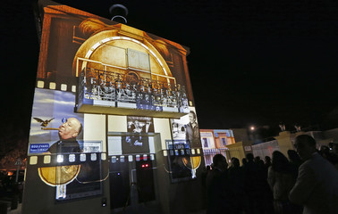 People watch a movie projected on the front wall of L'Eden cinema, the world's first and oldest cinema, during an inauguration of its reopening in La Ciotat