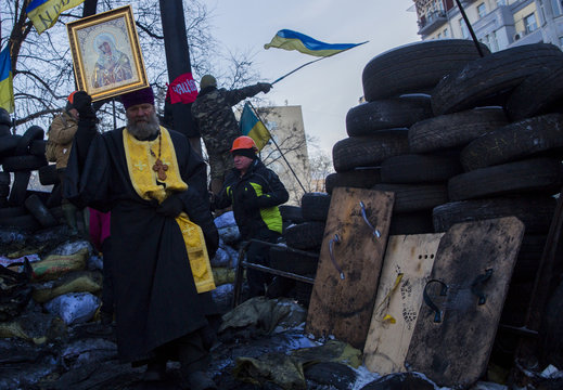 Father Valery holds an icon as he walks through barricades of anti-government protesters in Kiev