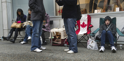 People and Frank the dog wait in line for the release of Apple's iPad 2 outside the Apple store in Vancouver