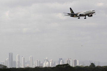 A cargo aircraft flies over the city skyline in Panama City