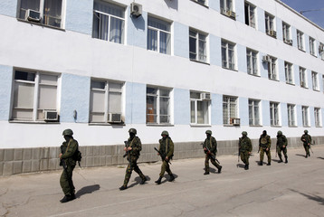 Armed men, believed to be Russian servicemen, walk on the territory of the naval headquarters in Sevastopol