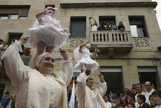 """Five-year-old girls dance on the shoulders of women during the """"Coca"""" celebration in Redondela"""