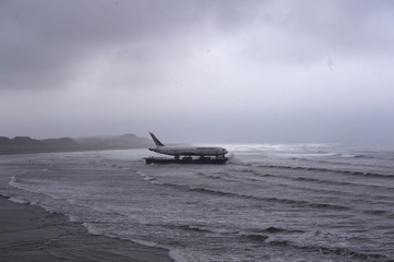 Bad weather surrounds a Boeing 767 airplane as it arrives onto Enniscrone beach after it was tugged from Shannon airport out to sea around the west coast of Ireland