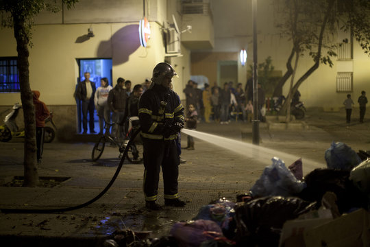A firefighter extinguishes burning rubbish bags, which were set on fire by residents frustrated by piling rubbish due to a strike by garbage collectors in Jerez de la Frontera
