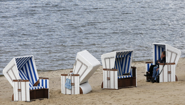 People sit in a beach chair during the first opening day at Wannsee lido, a public beach, in Berlin