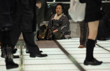 Stranded people rest at the Tokyo International Forum which has been converted to a temporary shelter after transportation was suspended in Tokyo