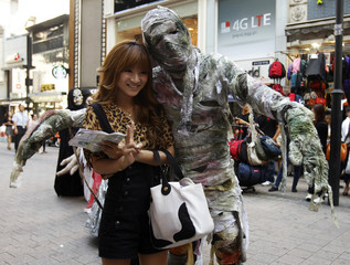 A woman poses for a photo with a performer dressed like a mummy, during a promotional event at the Myeongdong shopping district in Seoul