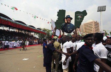 Supporters of Nigeria's President Goodluck Jonathan carry a map with the his picture on it during his declaration to seek a second term in the February 2015 presidential election, in Abuja