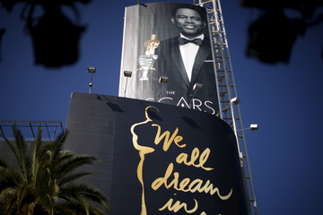 Oscars host Chris Rock is seen on a poster at the entrance to the Dolby Theatre red carpet on Hollywood Boulevard as preparations continue for the 88th Academy Awards in Hollywood, Los Angeles
