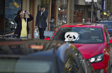 A woman takes a picture of a local landmark while standing near a large toy Teddy Bear sitting in the passenger seat of a parked car in Vancouver
