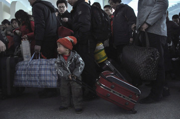 A child pulls luggage as he and his parents wait to board a train back to their hometown in Heilongjiang province